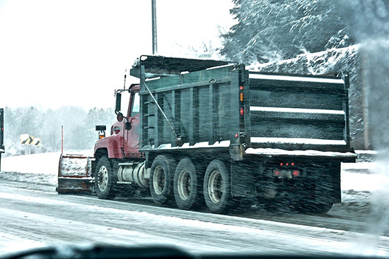 dump truck hauling snow on street